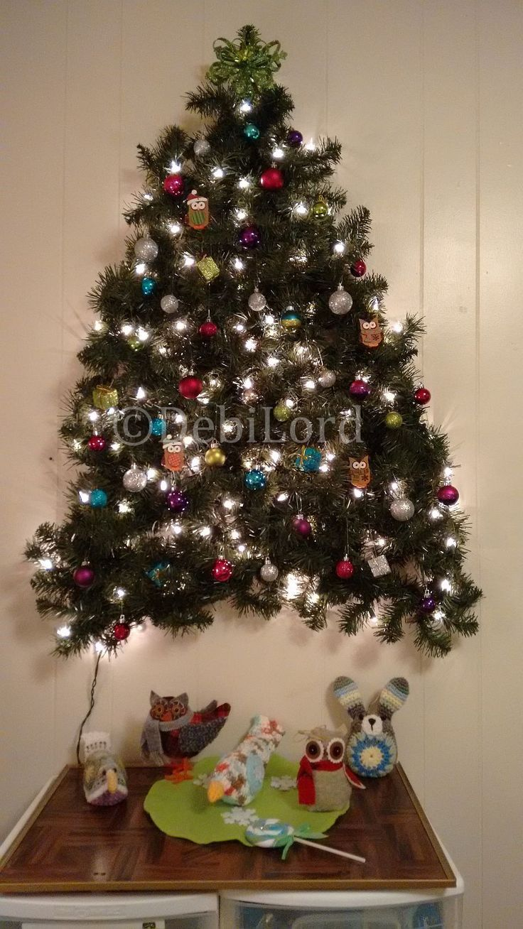 3-D wall Christmas Tree. I made this with two 9 ft strands of pre-lighted garland (connected to make it 18 ft.) and while flat on the floor, zig zagged into the shape of the tree. I then used zip ties to connect the rows to each other, then hung it on the wall attached to a sturdy screw.