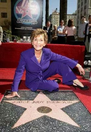 Judge Judy Sheindlin (born 10/21/1942) wearing purple.