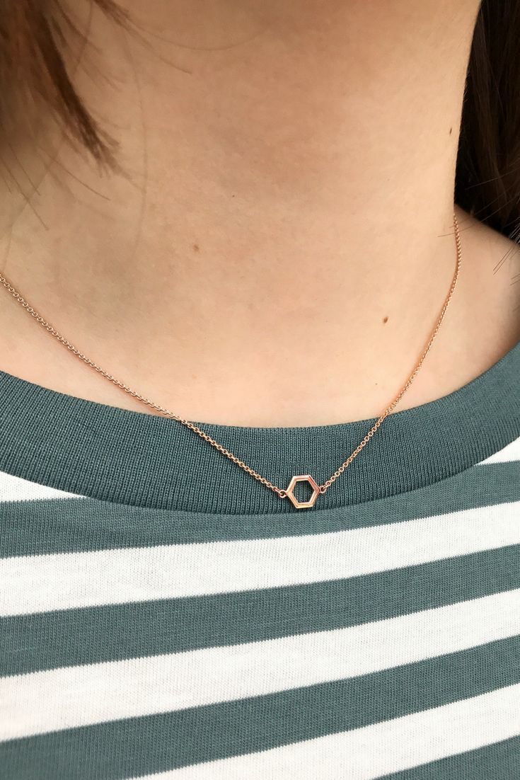 Crafted from 14K yellow gold, the Geo necklace lets the light shine through its hollow hexagonal pendant.