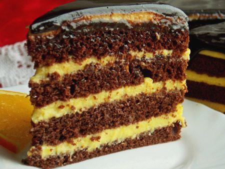 Deliciosul Tort cu crema de portocale si glazura de ciocolata este un desert minunat. Blatul de cacao impreuna cu crema cu