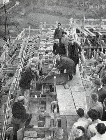 De bouw van het Groothandelsgebouw in Rotterdam: de laatste schep betonspecie wordt gestort door de voorzitter van de Raad van Beheer. Nederland, Rotterdam, 18 oktober 1951