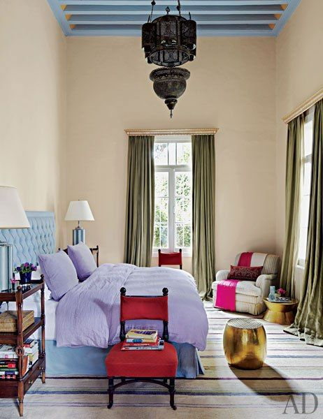 The antique lantern and the brass stool in the master bedroom are Lebanese. The ebonized slipper chairs are Italian, and the club chair, by O. Henry House, is clad in a Robert Kime ticking stripe; the bedside tables are from John Rosselli Antique