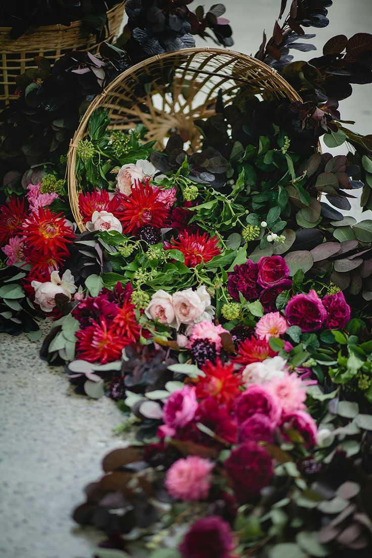 Pink and red flowers spilling out of woven baskets create a rustic wedding ceremony space | Elleni Toumpas Photography | See more: http://theweddingplaybook.com/modern-restaurant-wedding-inspiration/