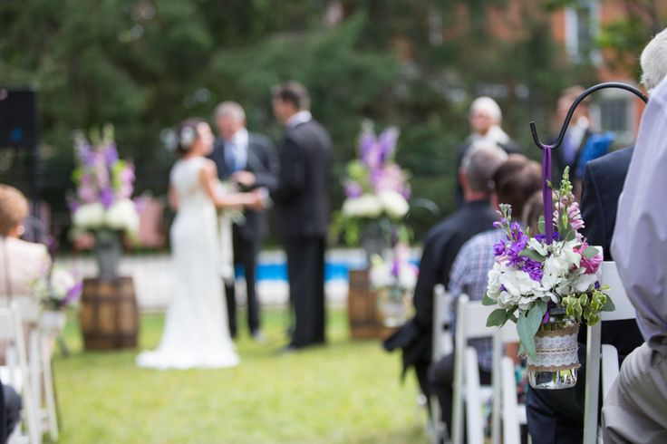 Love the flowers in vintage jars lining the ceremony aisle in outdoor wedding in Aylmer