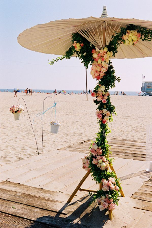 Umbrella decorated with flower garlands. Perfect for a beach wedding. For Julia
