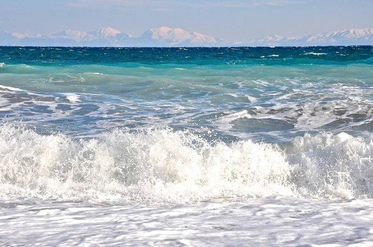Winter waves with on the back ground the snowy peaks of mainland Greece.