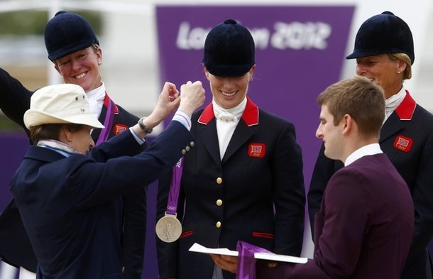 Britain's Zara Phillips (C) receives her silver medal from Britain's Princess Anne during the Eventing Team Jumping equestrian event victory ceremony at the London 2012 Olympic Games in Greenwich Park, July 31, 2012.
