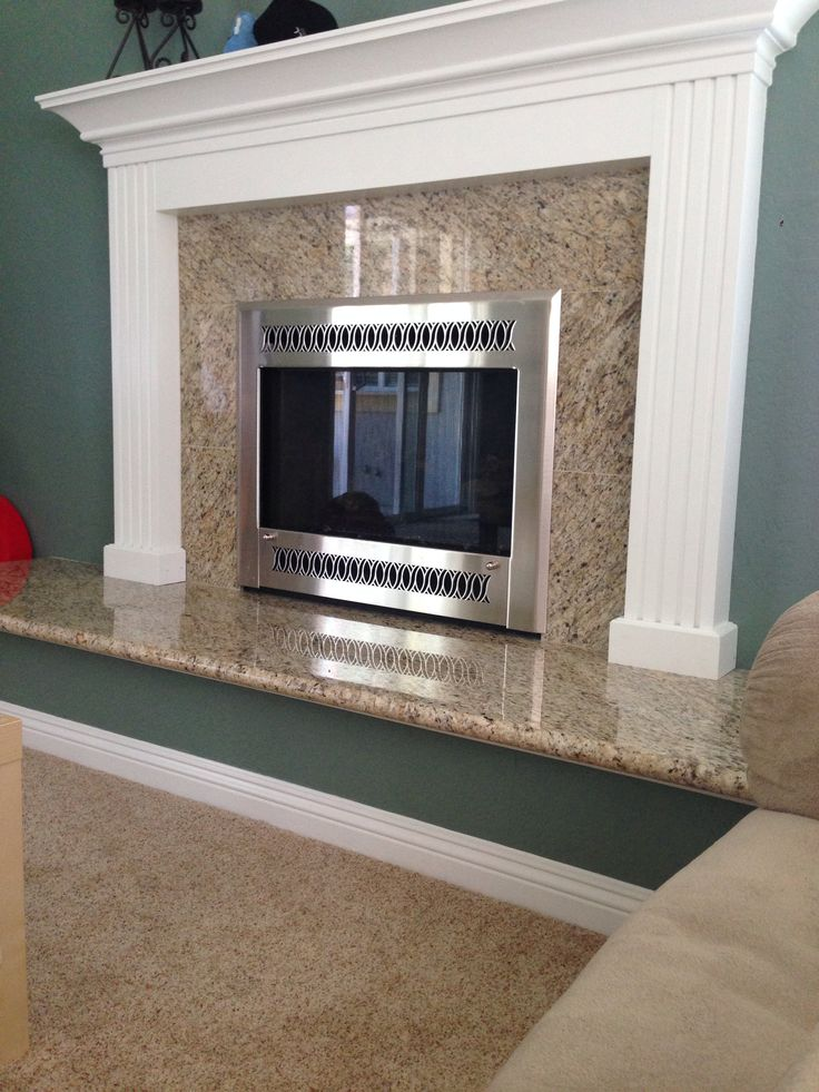 Granite fireplace hearth and tiled granite face with mantel. Hate the colors, but like the idea.