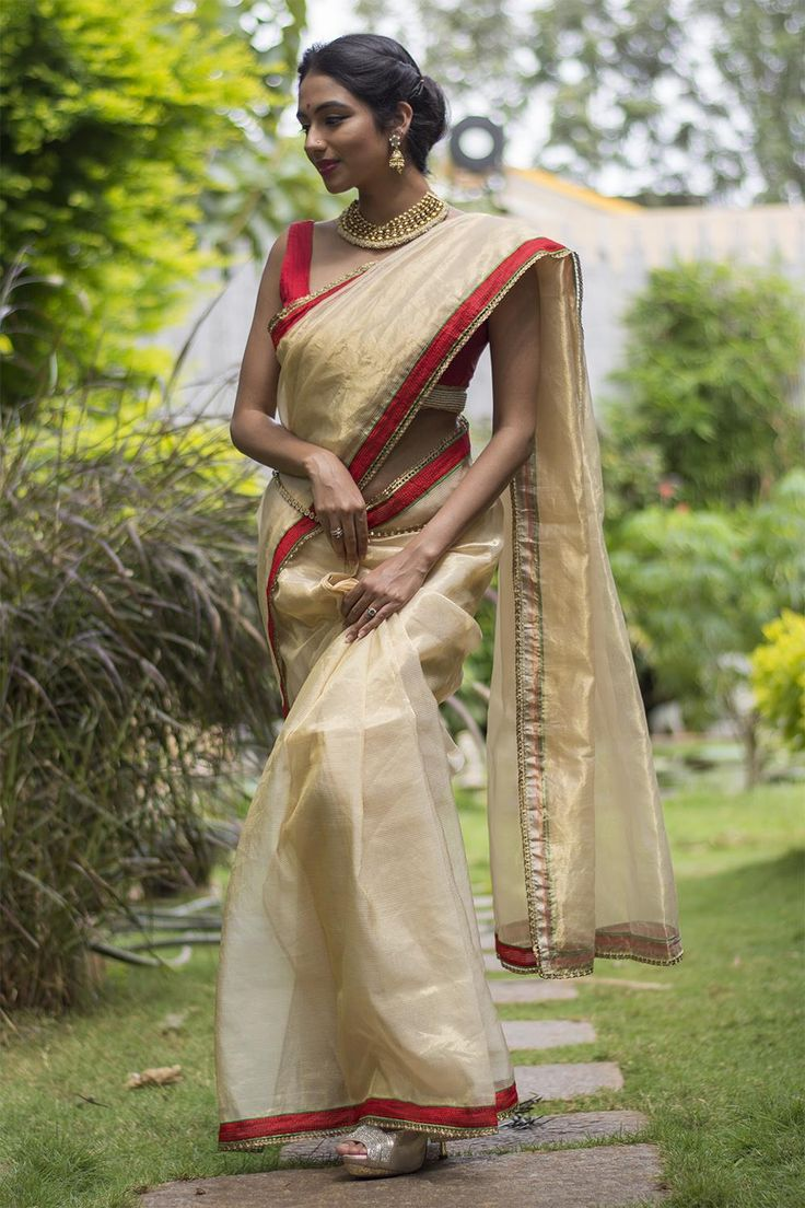 Shimmery and wispy...take this number any place. This lightweight gold tissue saree can work beautifully in a multiple of occasions. Don't want to be laden with a heavy silk? this gold tissue saree comes to your rescue!A red blouse, a green blouse or a shimmery gold blouse. This is not a demanding saree...pair away!ACCOMPANIMENTS: All sarees are sold completely finished with falls and a free size underskirt. FABRIC: Body: Beige gold tissue saree Details: Red green borderDISCLAIMER: Ships in…