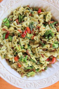A pesto pasta salad made with sundried tomatoes, artichoke hearts, asparagus, green and red peppers, and a tangy perfect lemon basil pesto dressing.