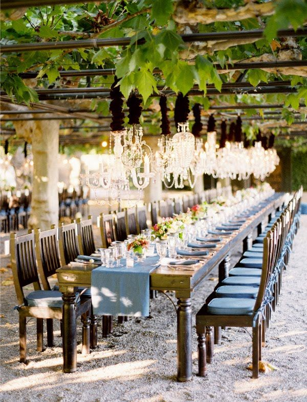 Love this long rustic table with chandeliers hung from the patio.