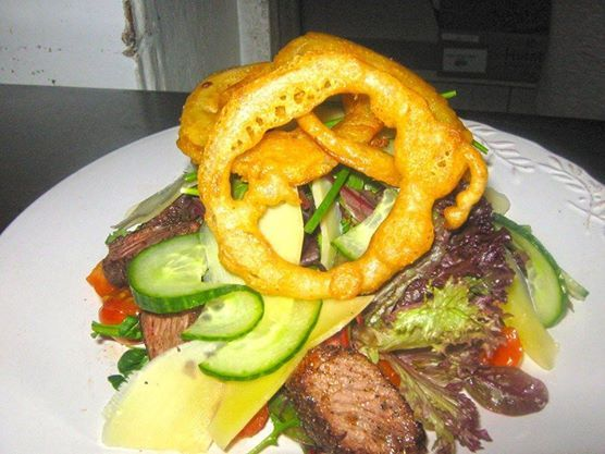 Salad doesn't have to be 'just greens' Have you tried our scrumptious Bonaparte salad? It's as big a hit in Blouberg as its' namesake was in France. Tender sirloin strips, covered with golden brown onion rings and spring onions, resting succulently on a bed of crispy garden lettuce. Come hungry!