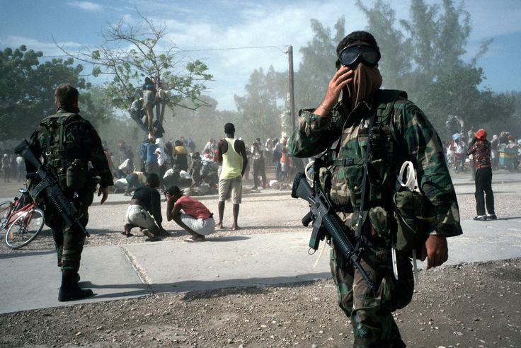 Alex Webb HAITI. Gonaives. 1994. The U.S. military and Haitians protect themselves from dust clouds created by the arrival of U.S. helicopters.