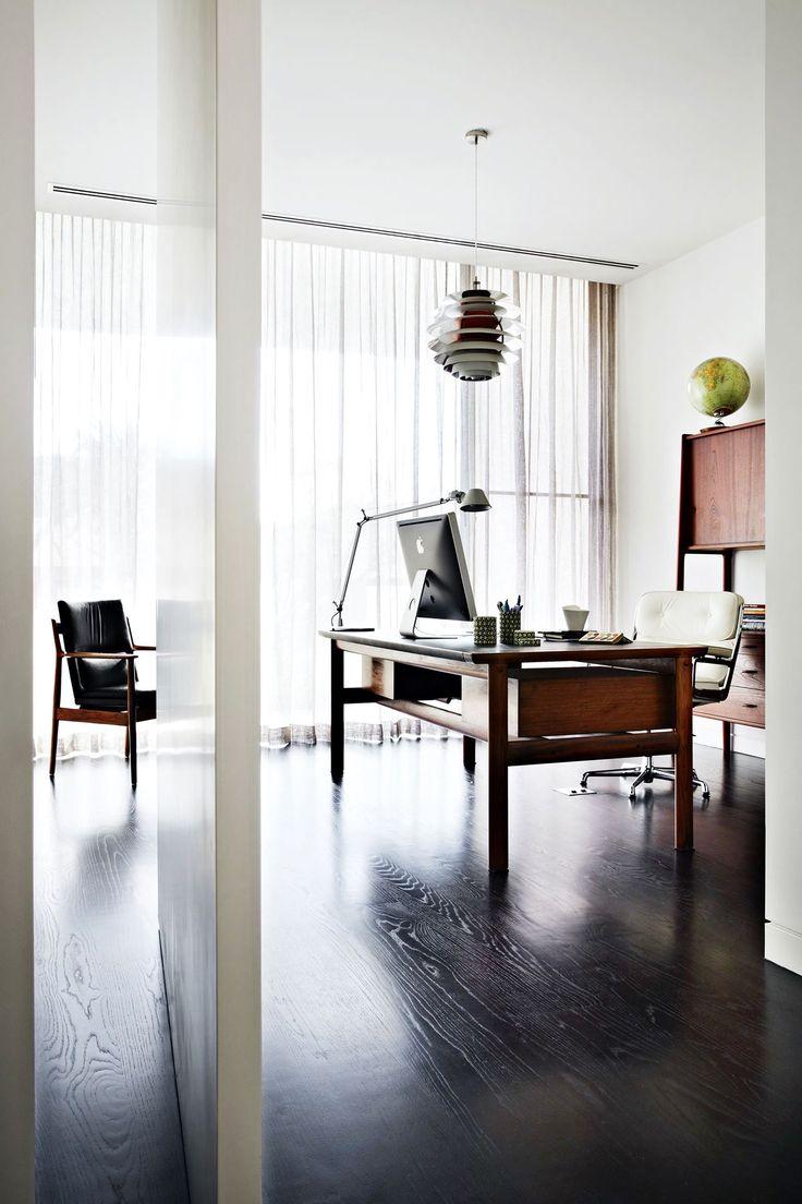 Mid-century modern workspace: rosewood desk by Danish designer Arne Vodder, Poul Henningsen pendant lamp, Eames white leather chair, dark floorboards, sheer white curtains