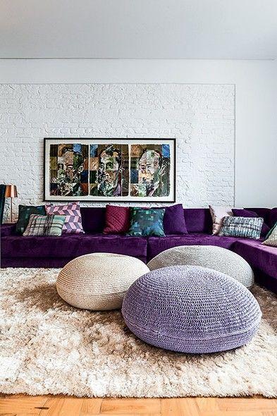 A sala de TV do arquiteto Thiago Passos ficou marcante com o sofá púrpura e os pufes de crochê (um deles em lilás)