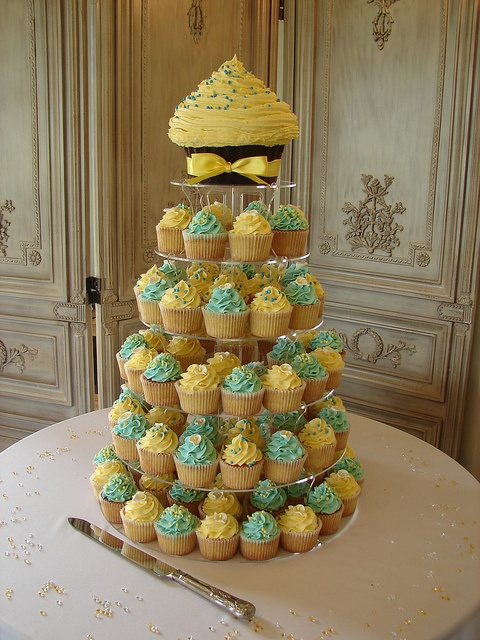 Turquoise and yellow cupcake tower!  --love the idea of the giant cupcake on top