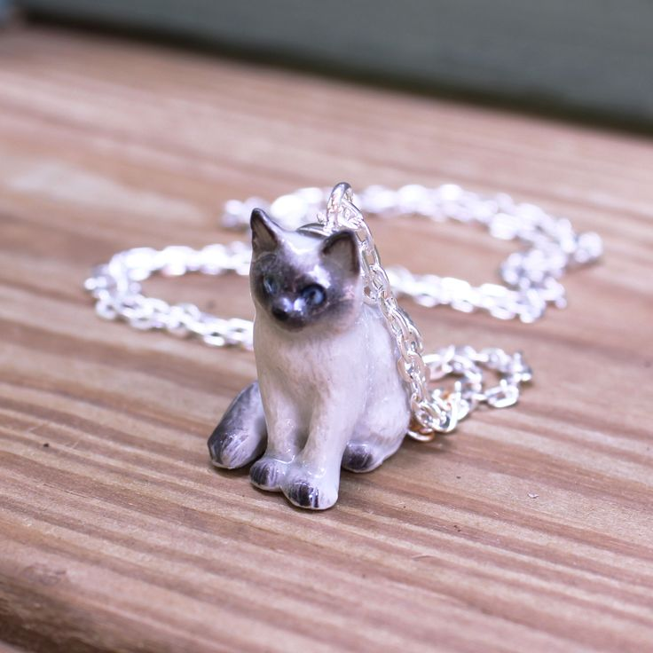 """I didn't know what my life was missing until I came across this necklace. Handpainted, perfect and whimsical. This adorable ceramic Ragdoll kitten is hung from a 18"""" silver link chain."""