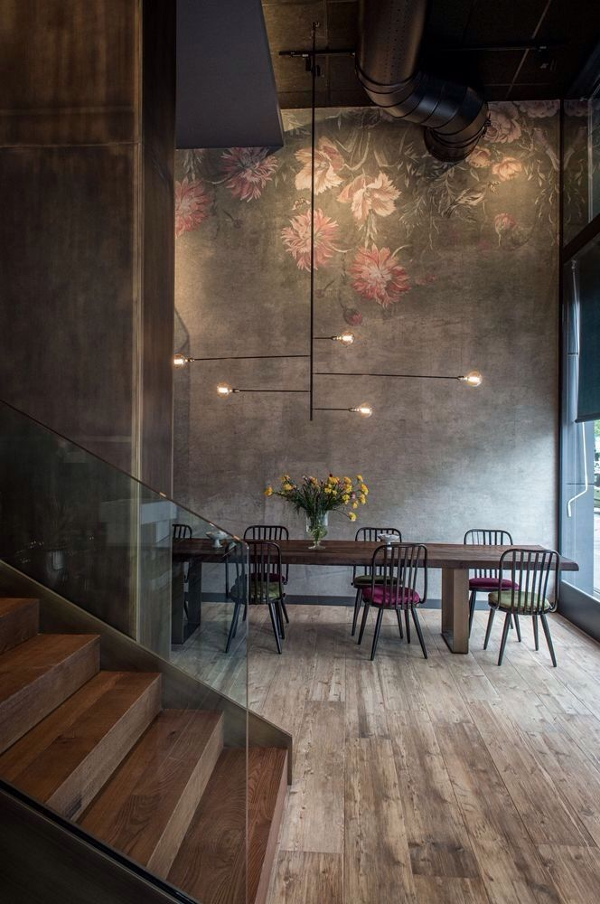 High ceilings in concrete, softened with a delicate pretty mural + unpolished wood flooring and stairs.