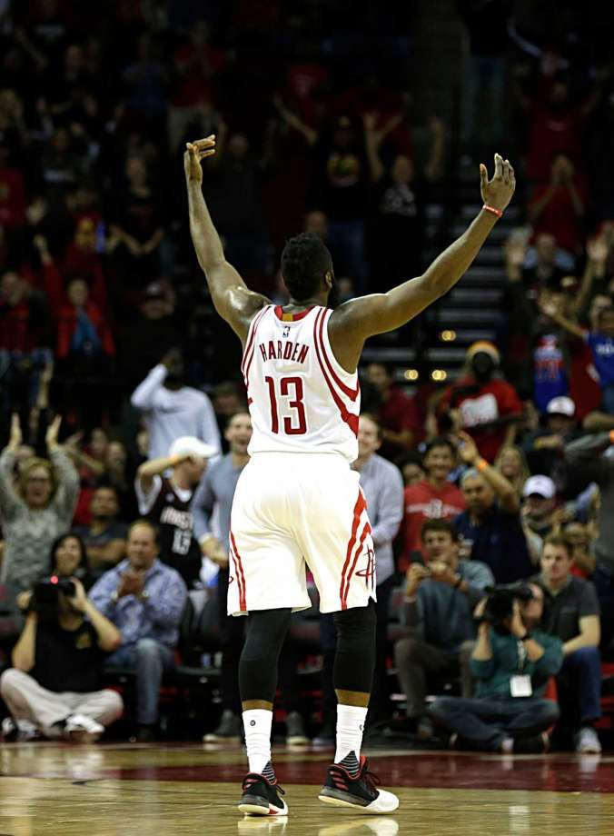 Houston Rockets guard James Harden raises his arms after scoring a three point shot with seconds