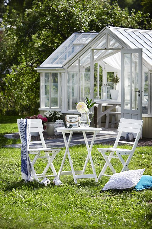 Simple white wooden table and chairs on the lawn.