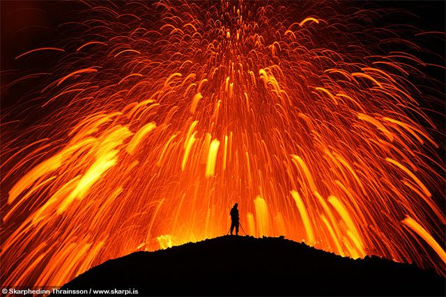 Photographer Joi on the edge of the crater of the erupting volcano in  Fimmvörðuháls/Eyjafjallajökull. Iceland Apr 2010. While observing  this photo ST was amazed how relaxed Joi actually is standing there while the volcano spreads melting lava around the area. ST guesses the lava is about 1000-1200°C at this point.