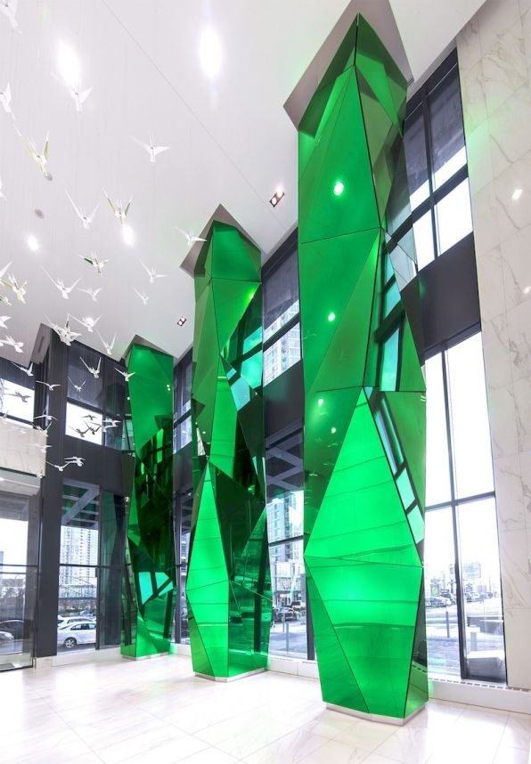 Vibrant green, mirrored, multi-faceted glass columns soar in this new condo lobby, designed by Munge Leung. The columns are a dynamic accent adding life and vibrancy to the clean, sophisticated, modern space. Eventscape engineered, fabricated and installed these dramatic columns that are visible from the street.