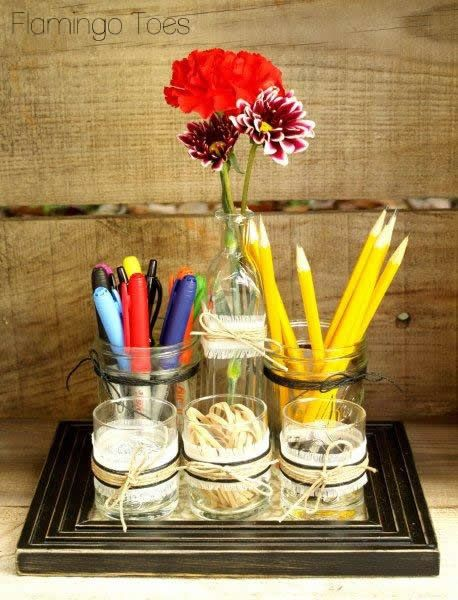 Another clever way to organize your desk without going out and buying something expensive--this idea uses an old picture frame and some jars, vases, and glasses! the ribbon/bows are a nice touch to pull it all together in a unified way. Now if only I had a vase or a picture frame...