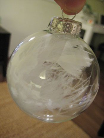 Feather-filled DIY ornaments. Craft glue, empty glass ornaments, bag of feathers (or