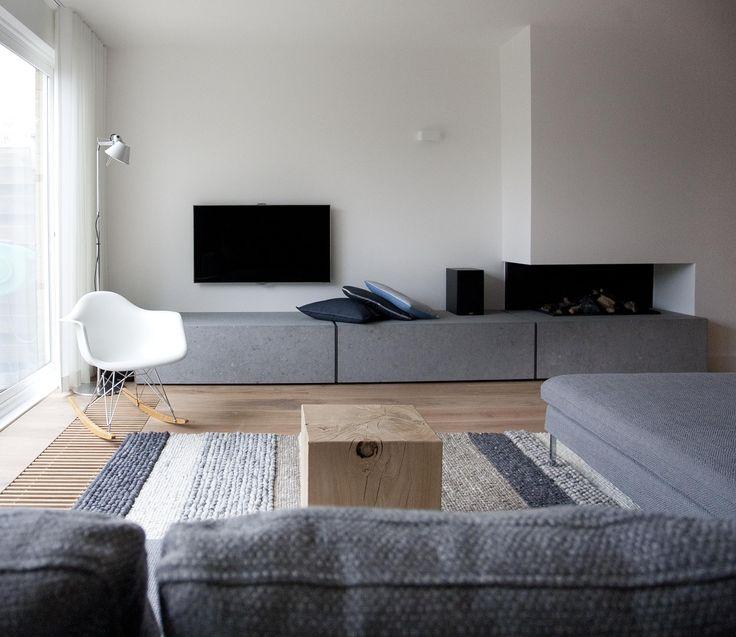 De bijzondere belijningen van de haardplateau gemaakt van beton maakt het geheel minder zwaar en past door zijn rustige en strakke uitstraling mooi bij de rest van het interieur..