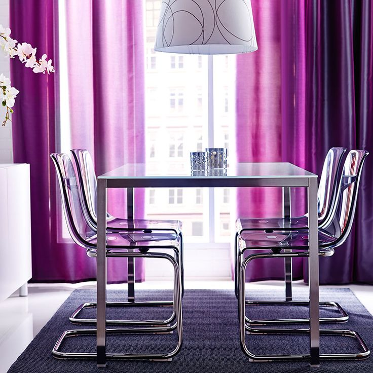 Mesa de refeição com tampo em vidro branco e pernas cromadas com cadeiras em roxo e estrutura de pernas em cromado