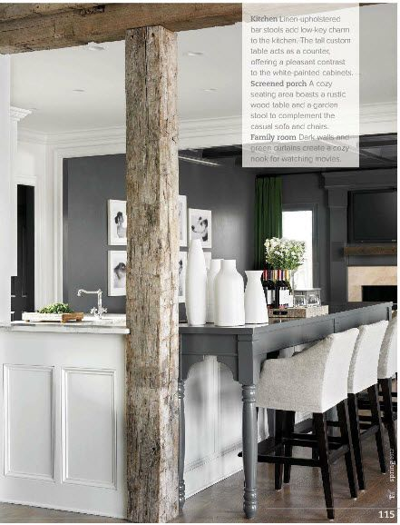 An island with the eating area designed as a furniture style table.  Gray mixed with white mixed with rustic wood post.