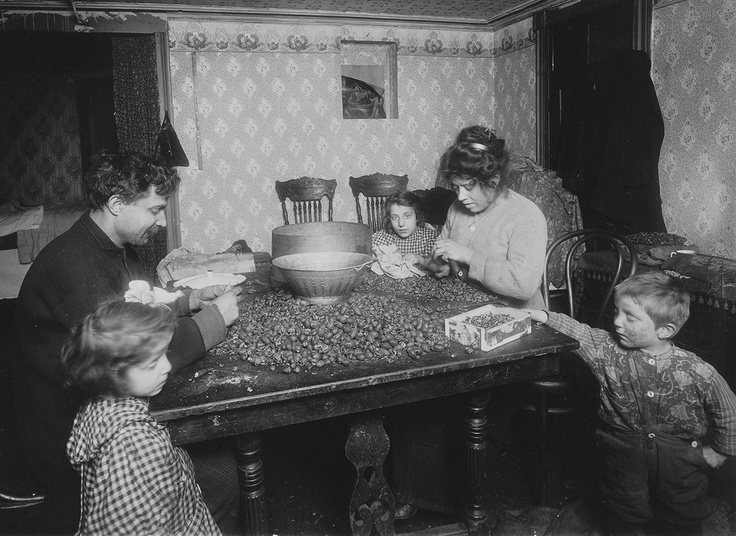 """""""Picking nuts in dirty basement. The dirtiest imaginable children were pawing over the nuts eating lunch on the tabel, etc. Mother had a cold and blew her nose frequently (without washing her hands) and the dirty handkerchiefs reposed comfortably on table close to the nuts and nut meats. The father picks now. New York City, December 1911""""  It's About Time: Photos"""
