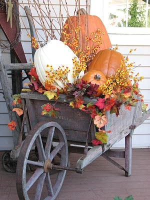 fall porch decor idea wheelbarrow with autumn leaves and pumpkins - Harvest Decorations