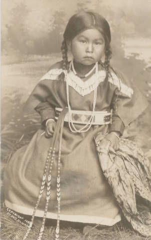 1899 Unidentified Nez Perce girl wearing necklaces over beaded dress holds shawl .