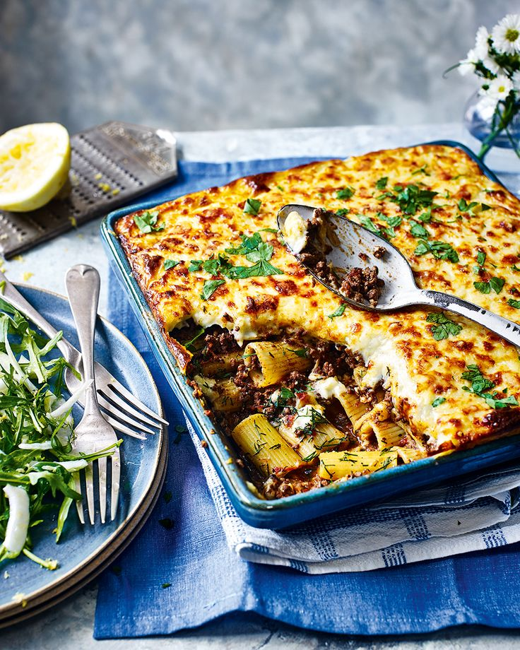 Rigatoni is topped with a rich meat sauce and a thick layer of béchamel in this irresistible Greek-inspired pasta bake recipe. This dish is the perfect indulgent family meal.