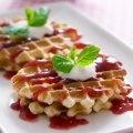Esta receta básica de wafles va servida con una salsita de fresas. La puedes sustituir por miel de maple y un poco de crema batida.