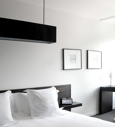 Hotel Albert Premier in Luxembourg - minimalist bedroom with crisp white bedding, retro alarm clock, and frames to the side rather than above the bed