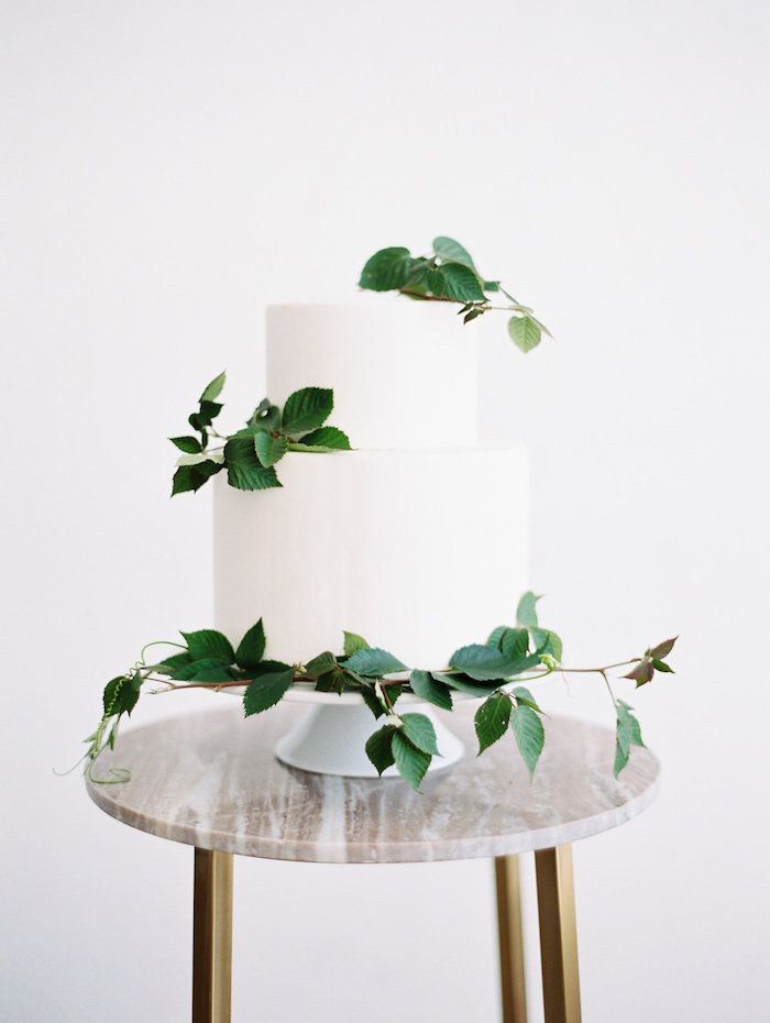simple two tiered white wedding cake with green vines