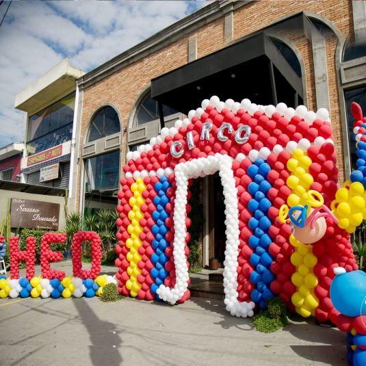 Circo do Theo Da GiraGirassol, o circo montado na fachada do buffet Spasso Dourado, em Pirituba (SP), para Theo, um ano, foi feito com balões Happy Day. O cenário contou com tenda, letras em balão e palhaço. Tudo em balão. A decoração da mesa, feita pela própria mãe, foi delicadamente emoldurada por modernos arranjos de pé de balões gigantes nas cores do tema.