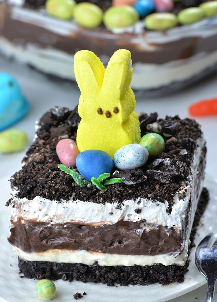 Four layered Easter Chocolate Lasagna garnished with Oreo dirt on top, Peeps Bun…
