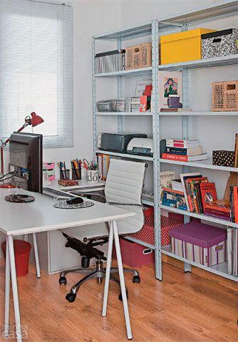 As estantes de aço, repletas de caixas, e a mesa com cavaletes se encarregam de organizar o espaço do escritório desta professora. São três unidades de aço. A cadeira é de aço cromado e couro ecológico. O piso é laminado. Projeto da arquiteta Juliana Savelli.