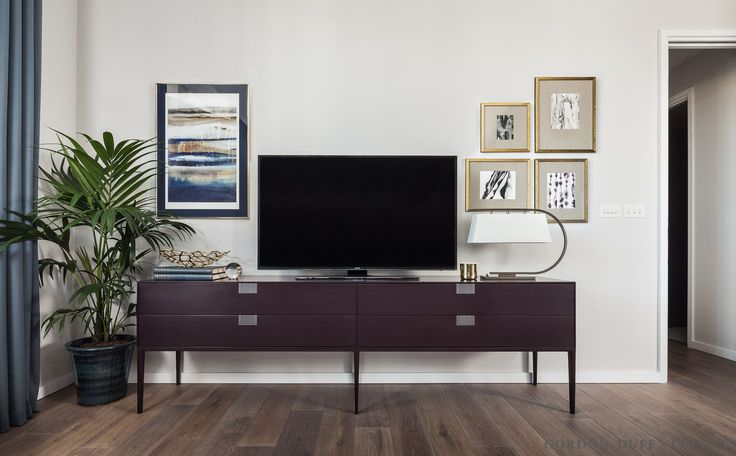 Living room view of console B&B Italia sideboard and gold framed pictures. Natural wood floor.
