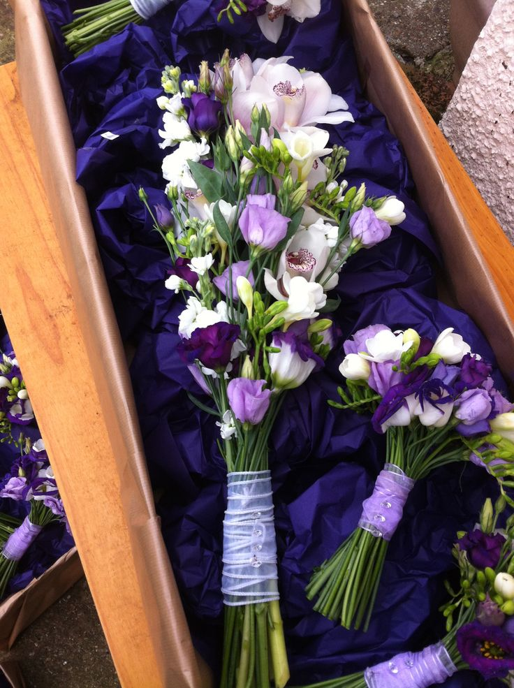 Sheaf style bouquet of cymbidium orchids and purple and lilac lisianthus