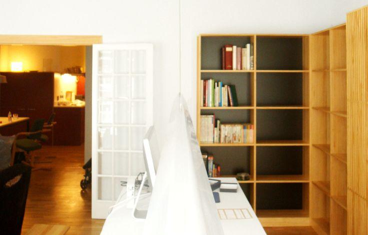 Zona de trabajo y estudio con estanterías de madera laminada y fondo negro. Diseño y reforma de 08023 Arquitectos - Barcelona