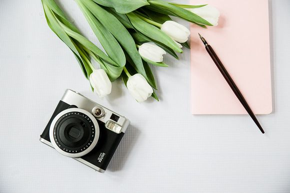 Styled Stock Desktop Photo by Petra Veikkola. This listing is for a single high resolution digital styled stock image of beautifully styled feminine desktop featuring white tulips, a calligraphy pen, insta camera and pale pink notebook. The image is feminine and elegant and gives your brand a beautiful boost.