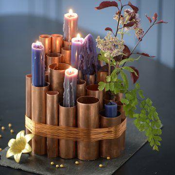 Ensemble de tubes de cuivre (à décliner avec des tubes en carton) de différentes hauteurs collés ensemble puis liés sur un socle rond en liège. Il peut servir de bougeoir, vase (avec des tubes à essai dans les tubes) ou comme support pour une décoration de Noël - tutoriel