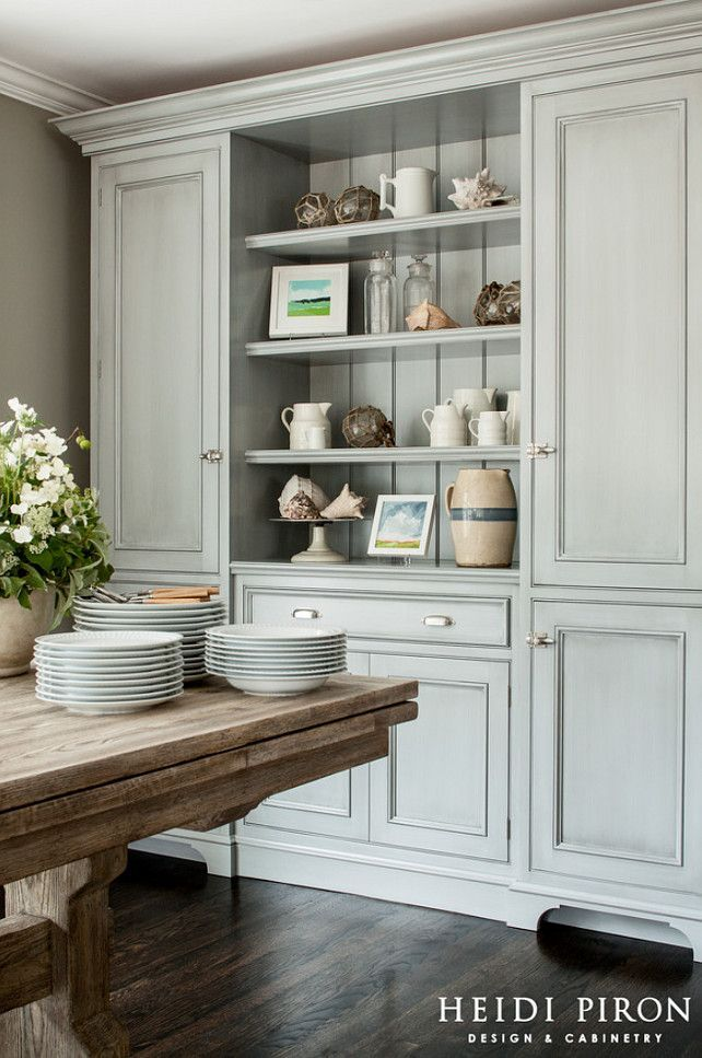 The blue-gray hutch in the dining area, an unfitted piece designed by the designer, provides storage for the kid's games and has built-in chargers inside for all their electronic devices.