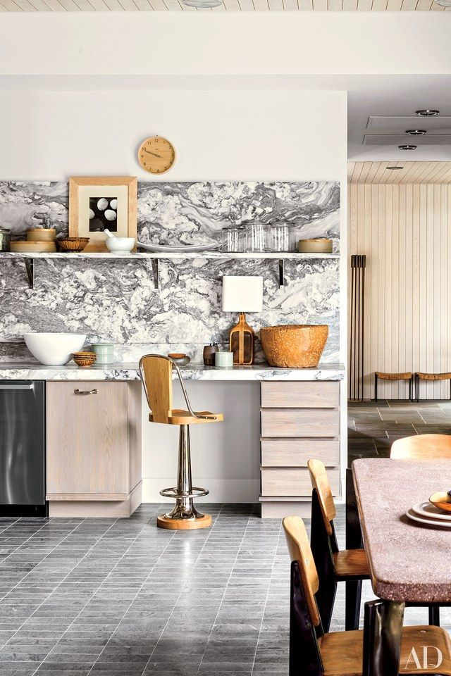Architect Deborah Berke and designer Thomas O'Brien ingeniously reimagined this Hamptons house. A Laura Resen photograph is propped next to the kitchen's wall clock, both from Aero | archdigest.com