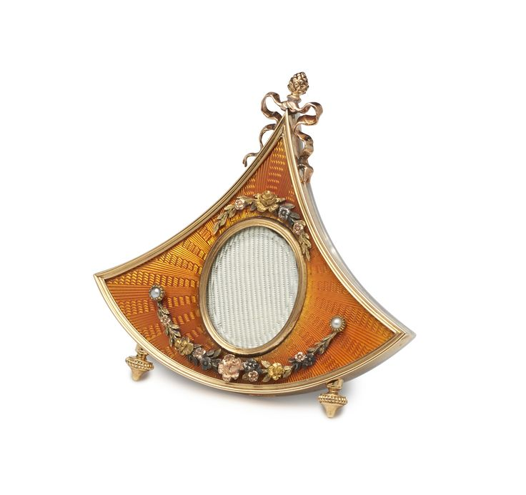 in the shape of an indented quadrant, enamelled translucent orange over a radiating dappled and linear guillochage, centred by an oval aperture held in a gold bezel, above a four coloured gold floral swag suspended from pearls and surmounted by a curved wreath of coloured gold flowers, topped with a bow tied pineapple finial, the reverse a panel of mother of pearl, supported on a scrolled silver gilt strut.  Workmaster: Johann Victor Aarne, St. Petersburg, 1896-1904