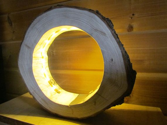 This log wood lamp can be hung on a desk, bedside table or even on the wall. Cut from a natural pine trunk, the wood was initially rough sawn. But then I sawed it and ground, so that there is a clean, smooth surface. The lighting itself is generated by an LED strip inside the wooden ring and has a very long life and very low power consumption.  Measurements: Outer diameter max. 31 cm, Inner diameter max. 19,5 cm, Thickness: 8 cm, Height. 27 cm,  Delivery without decoration